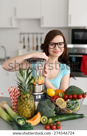 Smiling attractive woman preparing smoothies in her kichen beaming over the top of the liquidizer at the camera surrounded by fresh ingredients - stock photo