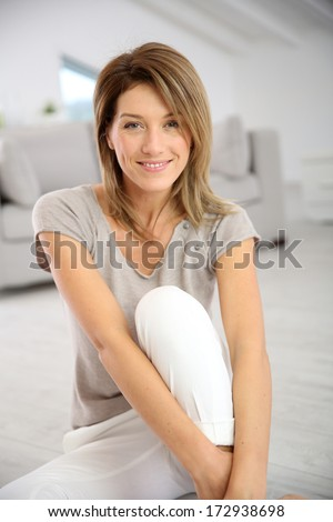 Smiling attractive woman relaxing at home - stock photo
