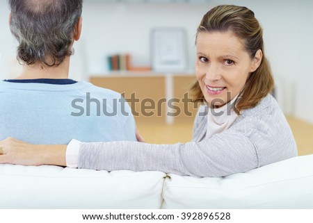 Smiling attractive woman relaxing with her husband on a couch at home looking back at the camera with a lovely friendly smile