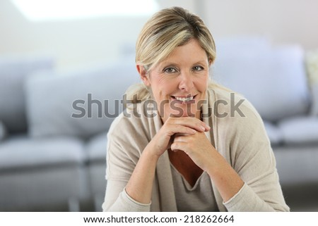 Smiling attractive woman sitting in sofa