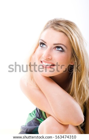 Smiling attractive young blond woman staring thoughtfully upwards as she relaxes with her head resting on her arm, isolated on white - stock photo