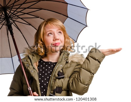 Smiling attractive young blonde woman standing under an umbrella holding out her hand to check for rain isolated on white - stock photo