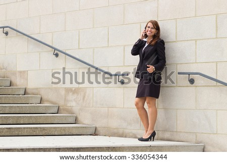 Smiling attractive young business woman executive talks on phone in urban environment - stock photo