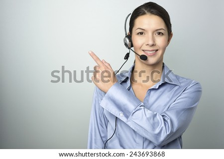 Smiling attractive young businesswoman with a headset pointing with her finger towards blank copy space on a graduated grey background - stock photo