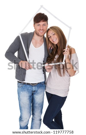 Smiling attractive young couple posing standing close together on a white background - stock photo