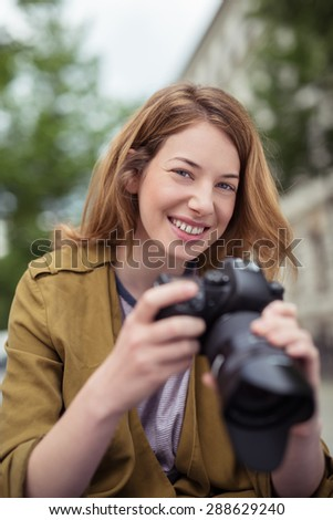 Smiling attractive young female photographer holding a professional Dslr camera as she photographs outdoors looking at the camera, focus to her face - stock photo