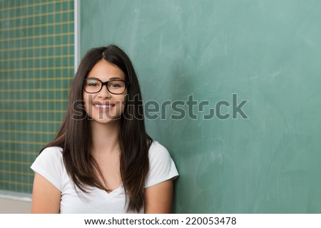 Smiling attractive young female student wearing glasses with long brown hair standing in front of a blank chalkboard looking at the camera - stock photo