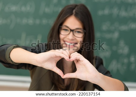 Smiling attractive young girl in glasses standing in the classroom at college making a heart gesture to show her love of school or that she has a sweetheart - stock photo
