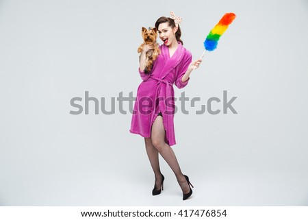 Smiling attractive young housewife standing and posing with dog and duster brush  - stock photo