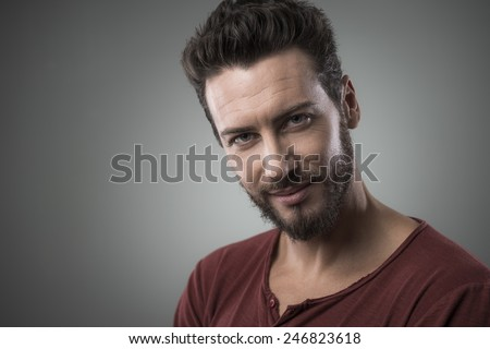 Smiling attractive young man flirting and smiling at camera