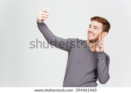 Smiling attractive young man in grey pullover taking selfie with smartphone and showing peace sign over white background - stock photo