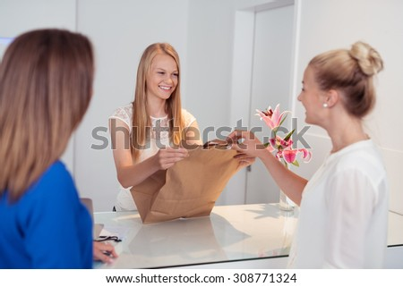Smiling attractive young shop assistant serving customers in a store handing over a brown paper packet over the counter with a lovely smile - stock photo