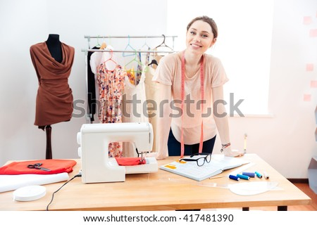 Smiling attractive young woman fashion designer standing and working in studio