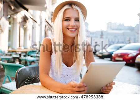 Smiling attractive young woman in hat sitting and using tablet in outdoor cafe
