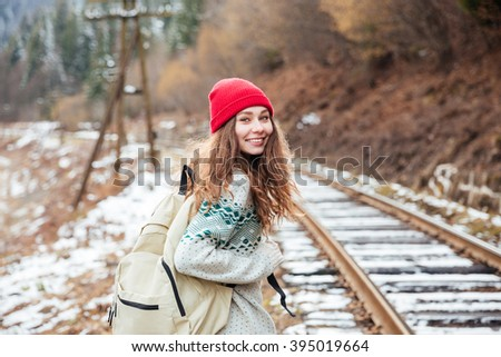 Smiling attractive young woman in red hat with backpack walking along railroad  - stock photo