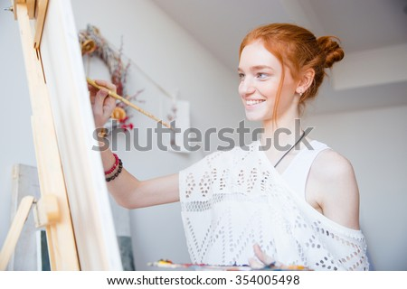 Smiling attractive young woman painter with red hair painting on canvas in artist workshop - stock photo