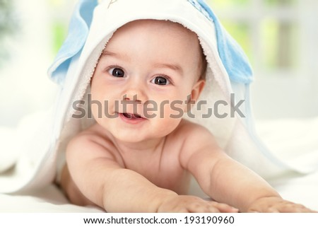Smiling baby after shower with towel on head - stock photo