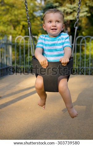 Smiling baby boy having fun on the swing in the city park - stock photo