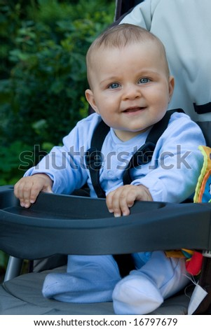 smiling baby boy in a pram outdoor