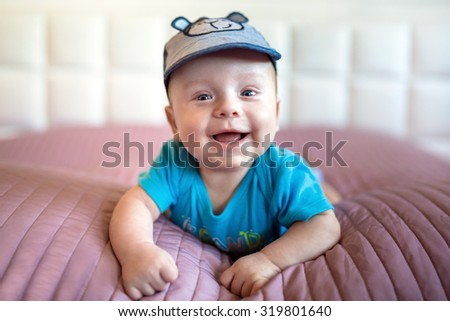 Smiling baby boy lying in bed - stock photo