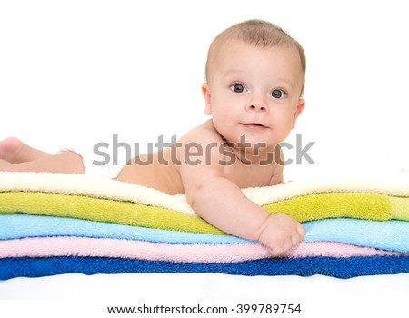 smiling baby boy lying on towels - stock photo