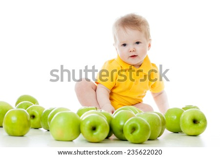 Smiling baby boy with many green apples - stock photo
