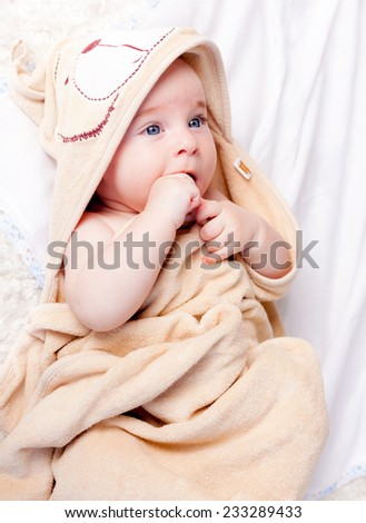 Smiling baby boy wraping into towel
