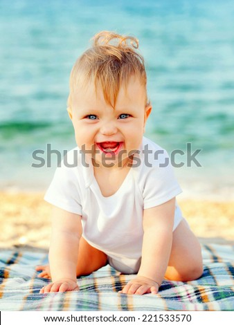 Smiling baby crawling on the beach. Happy childhood concept - stock photo