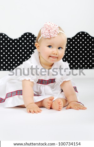 Smiling Baby dressed in white dress - stock photo