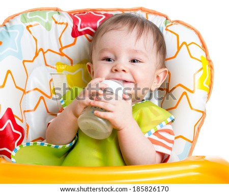 smiling baby drinking from bottle sitting in high chair - stock photo
