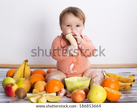 Smiling baby eating banana and many kinds of fruit and bowl with yoghurt - stock photo