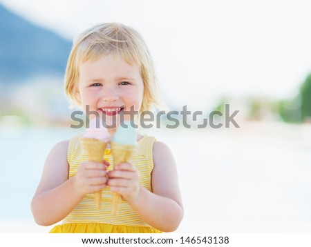Smiling baby eating two ice cream horns - stock photo