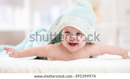 Smiling baby girl after shower with towel on head - stock photo