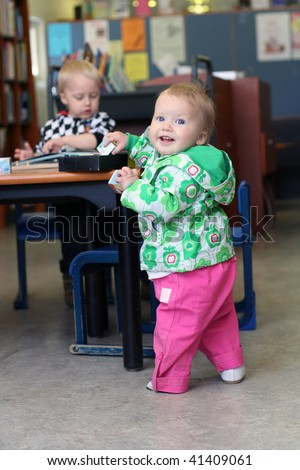 Smiling baby girl and elder brother in library