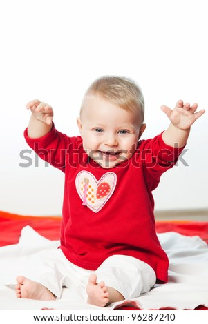 Smiling baby girl in red dress with white heart on it - stock photo