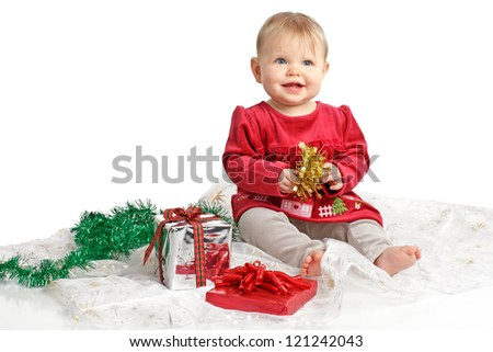Smiling baby girl in red velvet dress and gray stretch pants holds shiny gold bow. She sits near wrapped holiday gifts and green garland. Isolated/cut out, white background, horizontal, copy space.