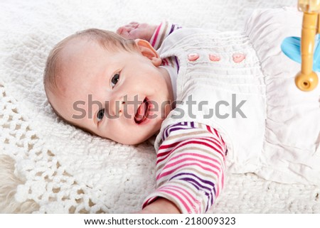 Smiling Baby Girl Lying on Back on White Blanket and Looking at Camera