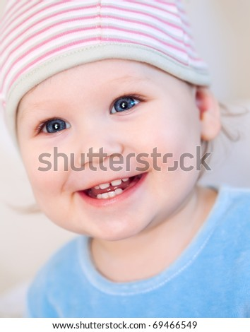 Smiling baby girl showing teeth wearing a  hat isolated