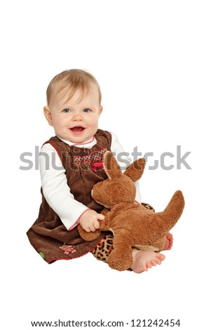 Smiling baby girl sits and plays with stuffed toy kangaroo. She wears a brown velvet embroidered dress with leopard print pants. Isolated/cut out on white background, vertical, copy space. - stock photo