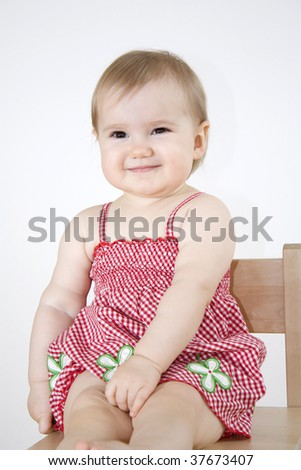 Smiling baby girl sitting on the wooden chair