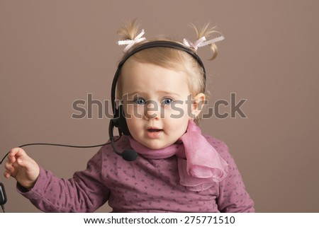Smiling baby girl taking a phone call - stock photo