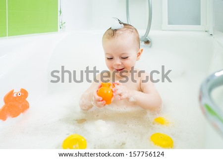 smiling baby girl taking bath and playing with toys - stock photo