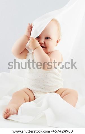 smiling baby girl under the white blanket. little funny child.newborn - stock photo