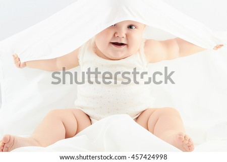 smiling baby girl under the white blanket. little funny child.newborn - stock photo