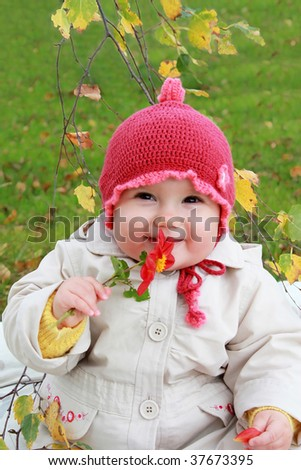 Smiling baby girl with autumn flower