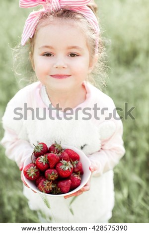 Smiling baby girl 4-5 year old holding bowl with strawberry outdoors. Looking at camera. Childhood.  - stock photo