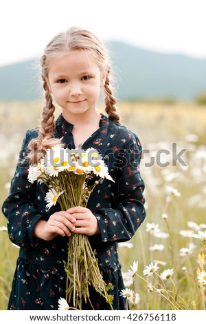 Smiling baby girl 4-5 year old holding chamomiles in meadow outdoors. Looking at camera. Childhood.  - stock photo