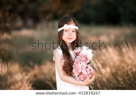 Smiling baby girl 4-5 year old holding peonies outdoors. Wearing stylish dress and headband. Looking at camera.