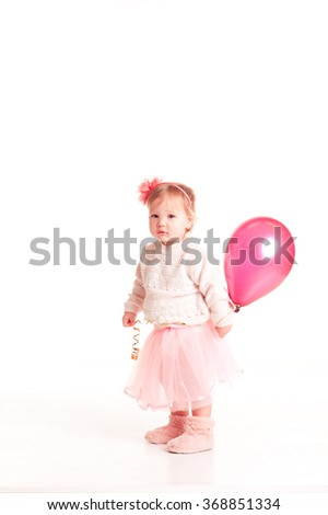 Smiling baby girl 1-2 year old holding pink balloon in room over white. Looking at camera. Childhood.