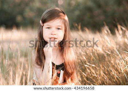 Smiling baby girl 4-5 year old posing in meadow. Looking at camera. Childhood.  - stock photo